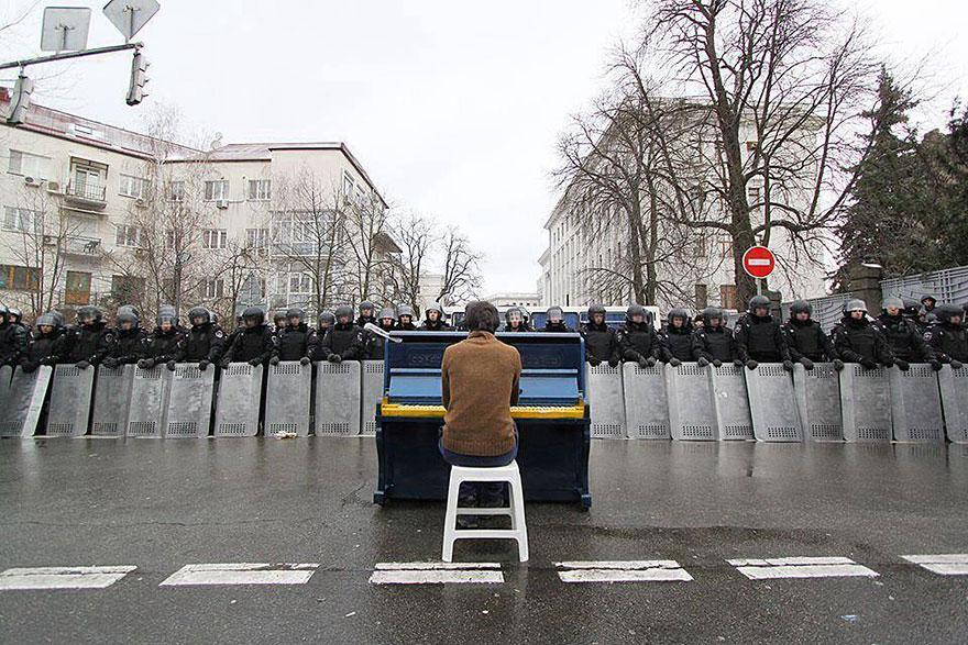 11. A Man plays piano for government's riot police
