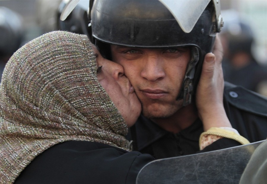 1. Cairo, Egypt (2011) - A woman kisses an anti-protest policeman while protesting against Mubarak's government.