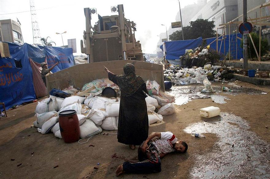 10. An elderly woman stands in front of a military bulldozer to protect a protester with gunshot wounds lying helplessly on the ground