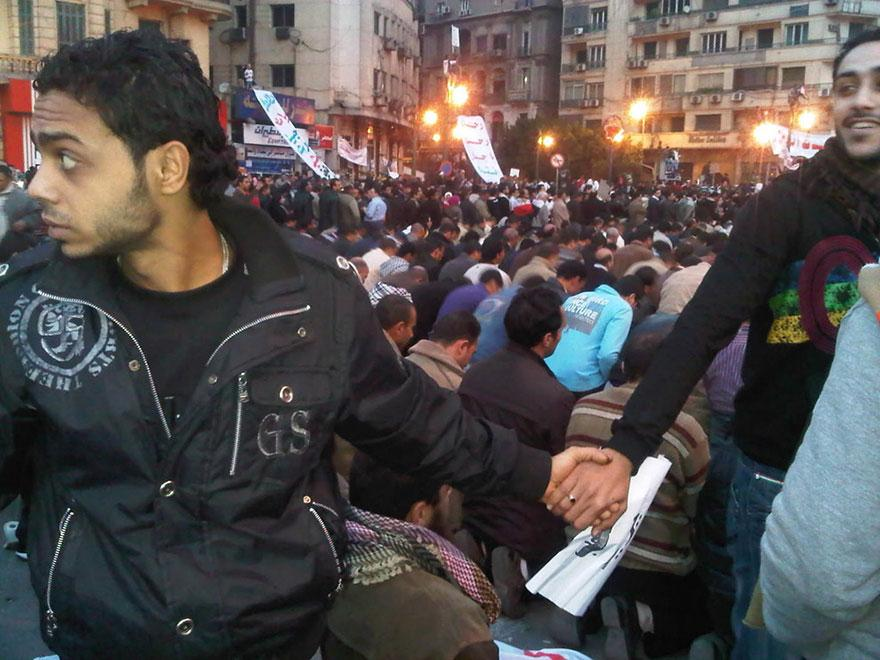 12. Christian protestors form a ring to protect muslim protesters as they pray during the revolution demonstrations