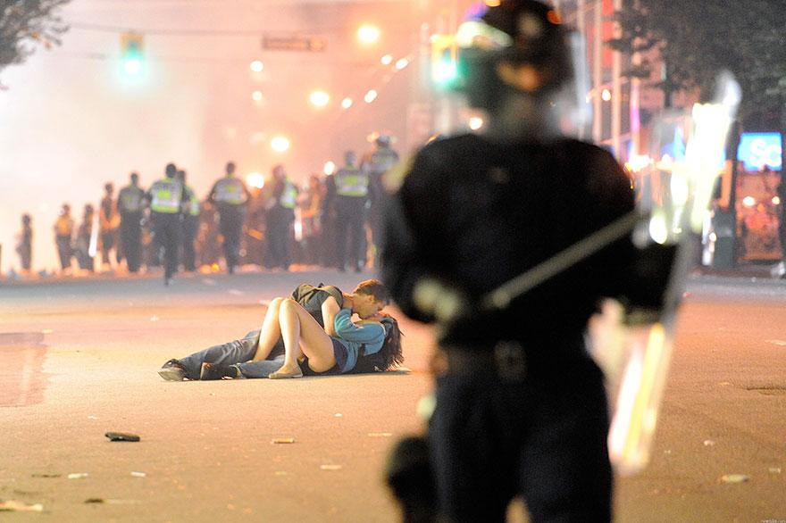 13. A couple risks it all to lay down and show love during a protest. Vancouver, Canada, 2011