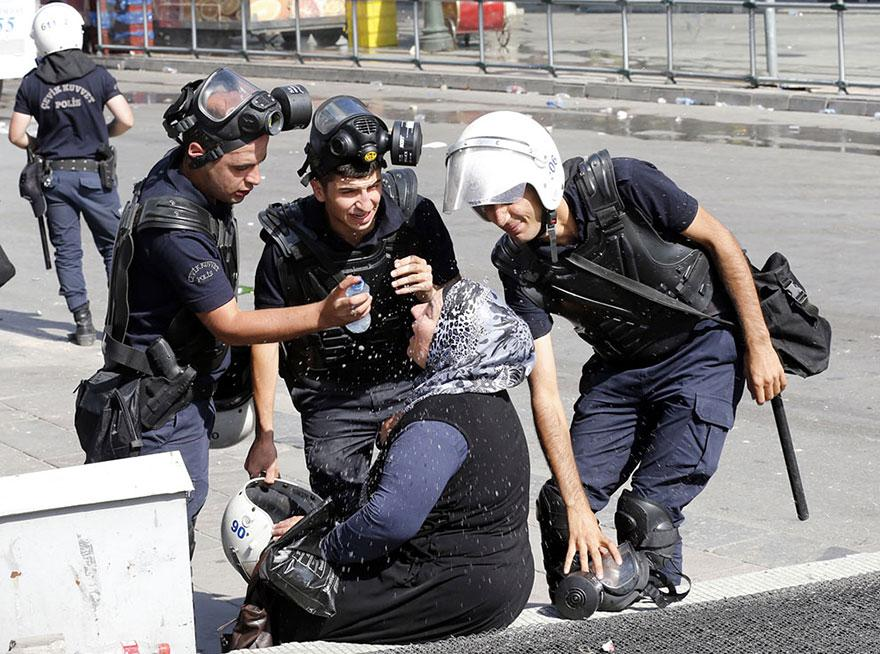 14. Riot police help an affected woman wash off tear gas