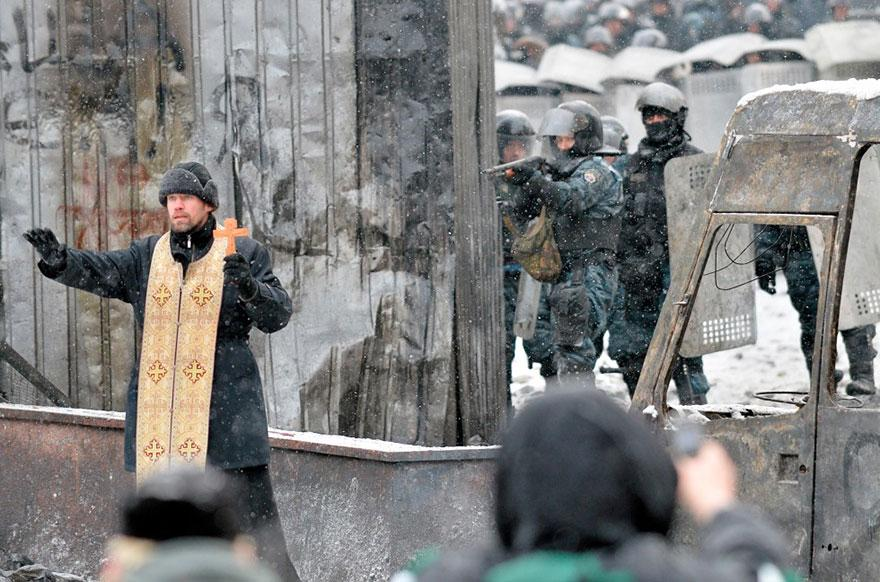 15. An Orthodox priest tries to prevent a clash between the police and demonstrators