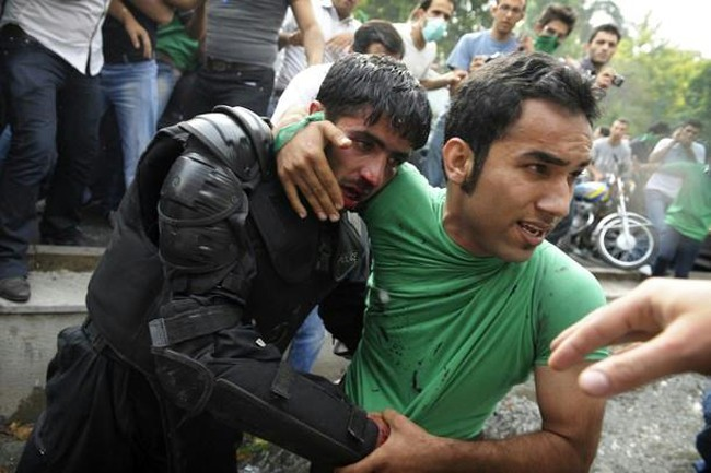 16. A protestor protects and escorts injured cornered riot police officer to safety after he was beaten by rioters.
