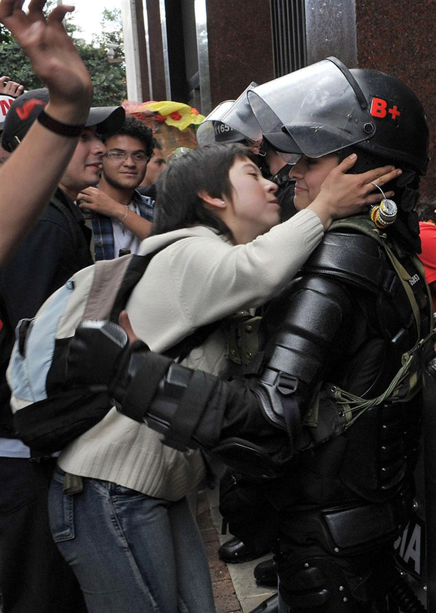 17. A student protester leans in to kiss a riot officer