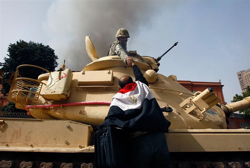 17. An Egyptian protester extends a hand of gratitude to an army soldier after they disobeyed orders to fire on civilians