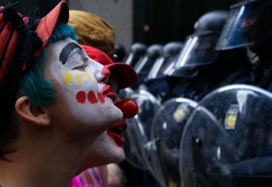 18. Protesters dressed as clowns entertain security offices outside a G20 meeting