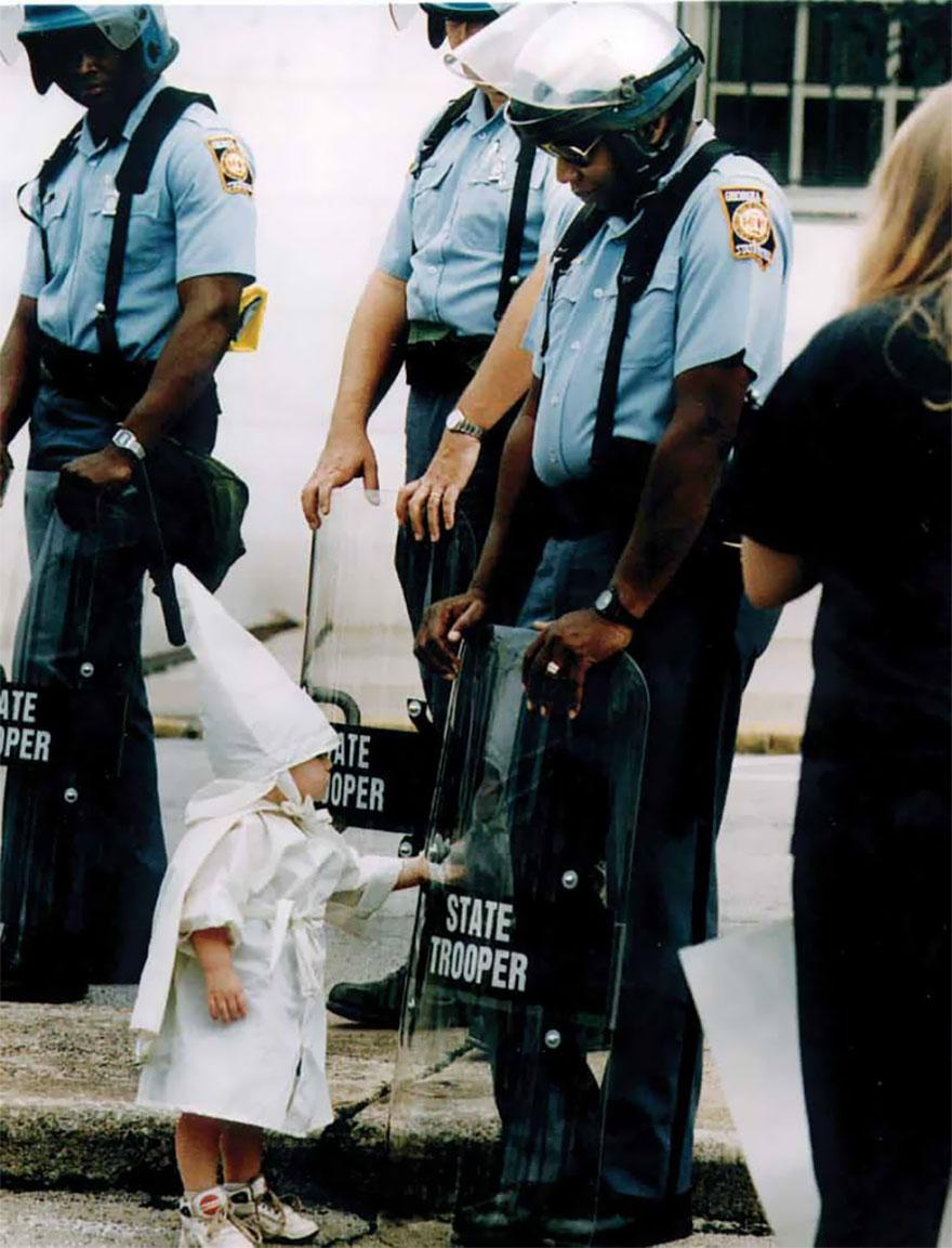 20. A young boy dressed in a KKK regalia admires his reflection in a riot shield held by an African AMerican Georgia state trooper