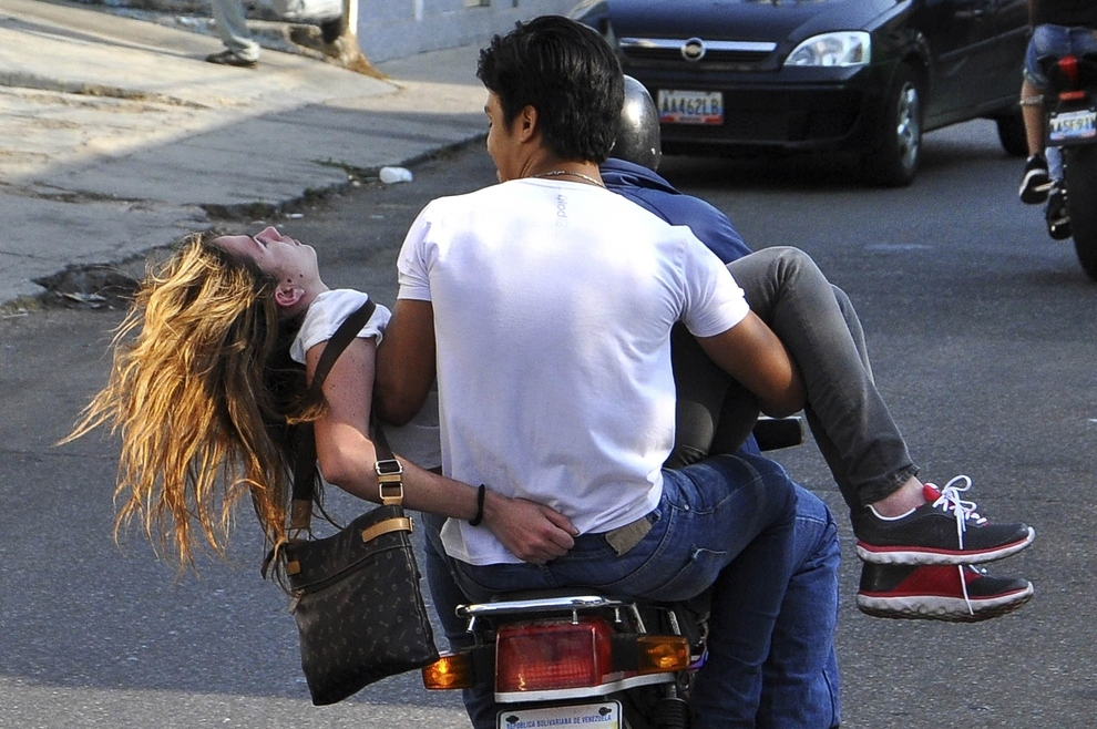 3. Valencia, Venezuella (2014) - Volunteers evacuate opposition supporter Genesis Carmona from the protest street after she was shot in the head during a protest against the government.