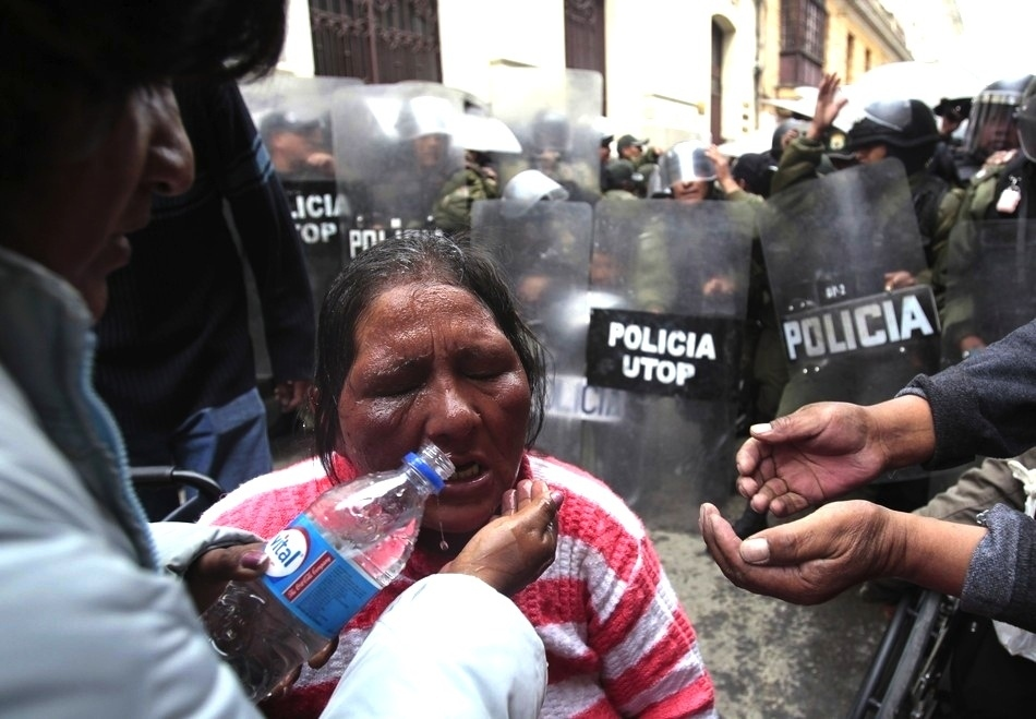4. Volunteers help a disabled woman wash off tear gas during a protest that turned violent