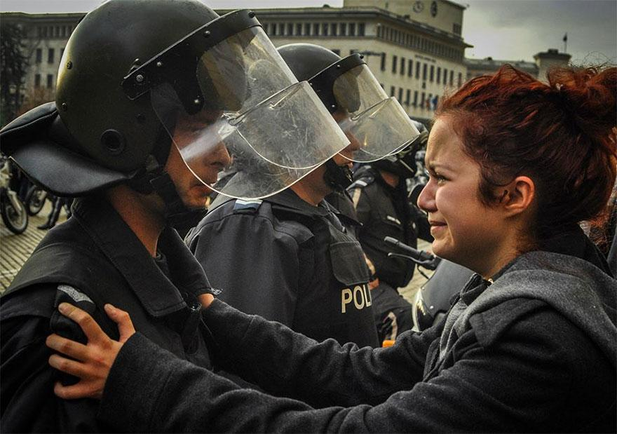 8. A law enforcement officer and a protester break down together in Sofia, Bulgaria