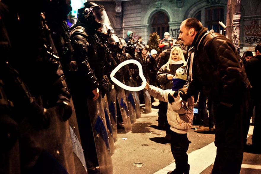 9. A young boy extends offer for peace in the form of a heart-shaped balloon to an anti-riot police officer in Romania.