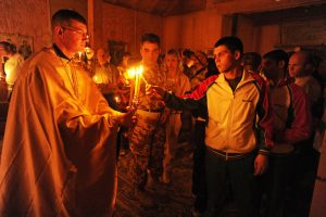 Capt. Sean Levine, chaplain, 117th Infantry Battalion, 2nd Stryker Brigade Combat Team, presents the trikeri or triple candle, which represents the Holy Trinity, for the observers to light candles during an Eastern Orthodox Easter or Pascha (a Christian version of Passover) service at Kandahar Airfield, Afghanistan, April 23.